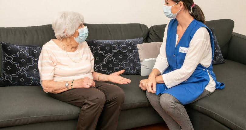 aide à domicile parlant avec une personne âgée
