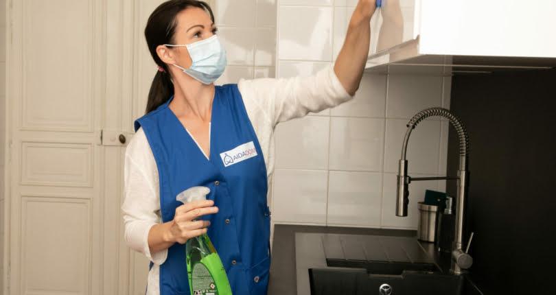 femme de ménage avec un masque nettoyant la cuisine